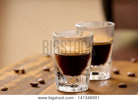 Glasses of espresso on wooden table