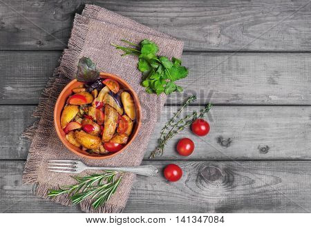 Steamed vegetables with rustic roasted potatoes eggplant zucchini peppers fresh cherry tomatoes rosemary cilantro basil thyme in ceramic bowl on light background gray wooden worn top view