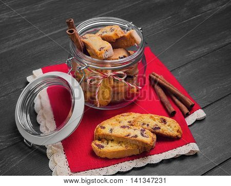 Italian biscotti cookies in a glass jar cinnamon sticks cookies biscotti scattered on a red lacy napkin on a dark black wooden background
