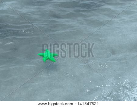 Toy form of sand in as starfish floating on the sea surface