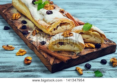 Cottage cheese and raisin cinnamon strudel with icing sugar ingredients for curd strudel raisins cinnamon sticks walnuts mint on cutting board blue wooden background