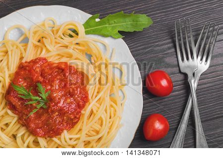 Pasta spaghetti with meat tomato sauce Bolognese sauce on white porcelain plate lettuce cherry tomatoes Bolognese sauce poured over spaghetti dark brown wood background top view