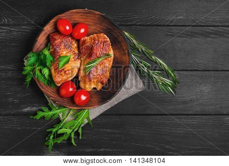 Two fried steak pork chops on wooden plate herbs to chop steak pork rosemary parsley cherry tomatoes lettuce black wooden background burlap top view