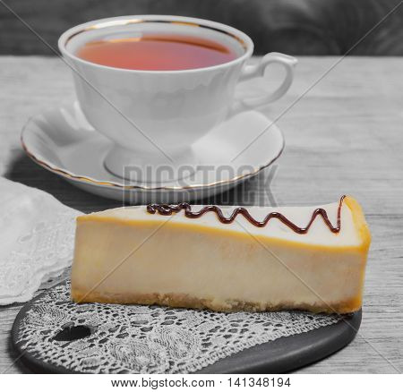 Cake Cheesecake classic New York decorated with chocolate white cup of black tea cloth on light wooden background surface