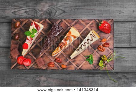 Assorted cakes cheesecake strawberry caramel chocolate caramel cut into pieces on wooden board fresh berries strawberry nuts chestnuts almonds pecans leaves mint gray wooden background top view