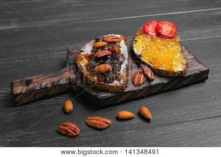 Sweet dessert sandwiches crostini with lemon jam plums pecans hazelnuts almonds rye bread on a cutting board on a black wooden background empty place for text