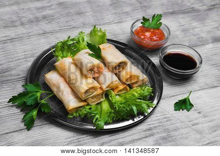 Little spring rolls on round metal tray plate light white surface lettuce parsley greens Fresh green onions soy sauce tomato sauce