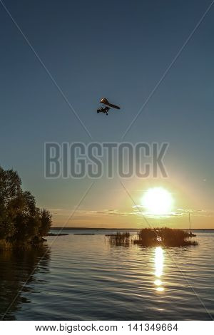 flight on a hang-glider with the motor over the lake against a decline
