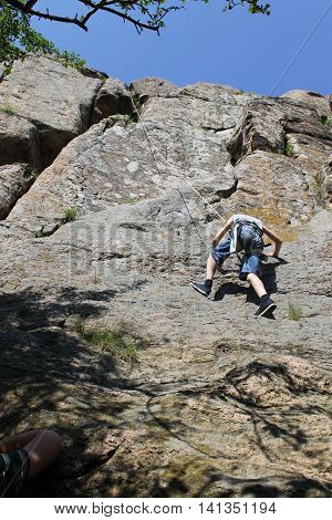 Boy rock climber climbs on the rock