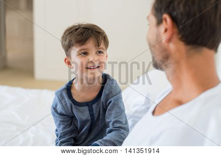 Father and son sitting on bed and talking to each other. Father and smiling little boy playing while sitting on bed. Portrait of happy child listening his father at home.