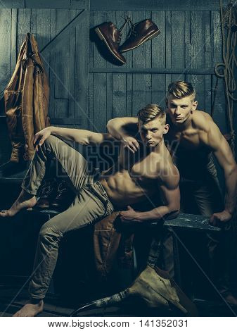 Two young male twins with sexy body showing their muscular torso and abs in studio