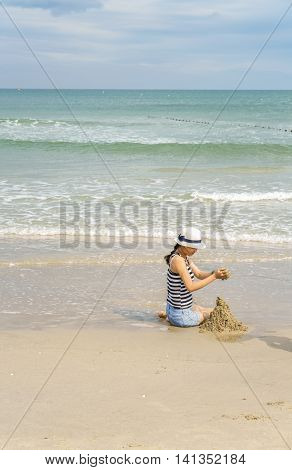 Young Girl Playing With The Sand At The China Beach
