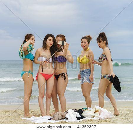 Young Girls Using Selfie Stick In China Beach In Danang