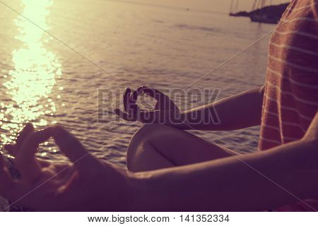Silhouette of a young woman practicing yoga on a rocky shore in Syvota bay Greece. Cloudy sky Ionian sea and a beautiful sunset in the background.