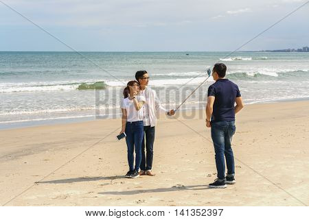 Young People Use Selfie Stick In China Beach Danang