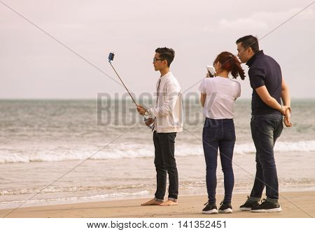 Young People Using Selfie Stick In China Beach Danang