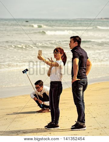 Young People Using Selfie Stick In China Beach In Danang