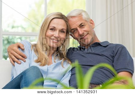 Romantic senior couple sitting on a sofa and looking at camera. Portrait of a mature couple enjoying their retirement. Happy smiling senior couple embracing together at home.