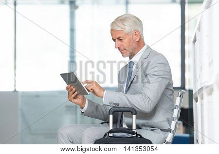 Senior businessman using digital tablet at office in waiting room. Mature leader checking email with laptop at airport. Business man sitting at the airport terminal in a waiting lounge with luggage.