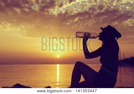 Young woman sitting on the rocky shore drinking water and enjoying a beautiful sunset in Syvota bay Greece