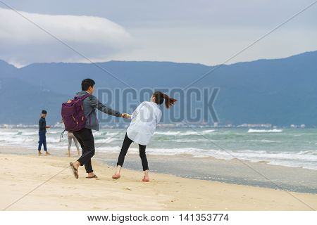 Young Couple Holding Hands At The China Beach In Danang