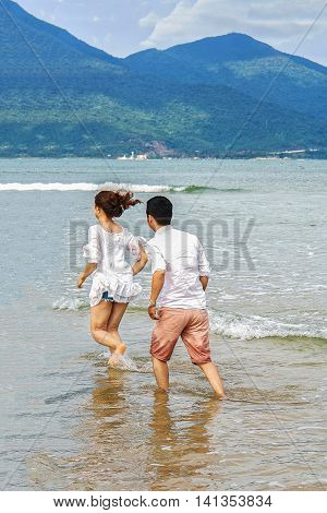 Young Couple Running Through The Water In The China Beach Danang