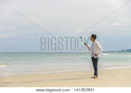 Young Fellow Using Selfie Stick In China Beach In Danang
