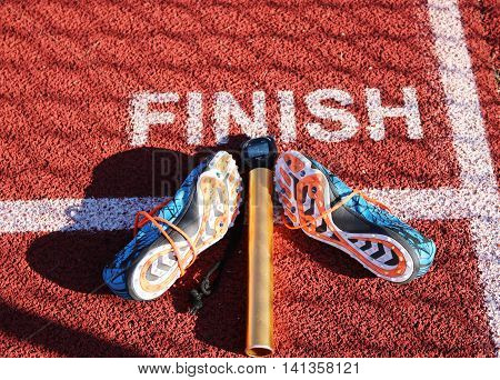 The finish line in track and field with a pair of spikes, a stop watch and a baton.
