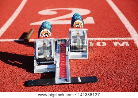 A set of starting blocks with spikes in and baton ready to race, picture taken from behind the blocks.