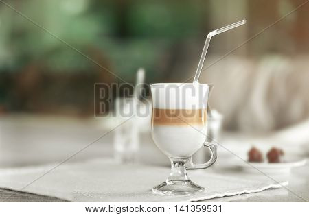 Glass of latte with straw on table in cafe