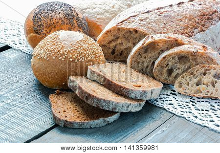 rye bread bun with sesame seeds and bun with poppy seeds lying on a wooden board and white napkin with lace