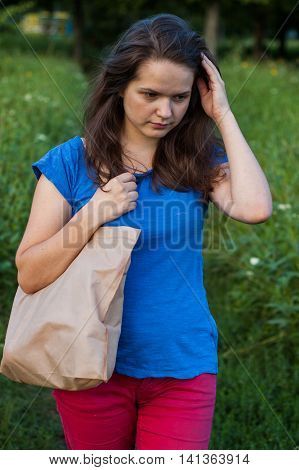 woman with shopping bags goes from shop