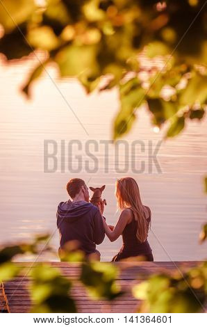 Rear view of a romantic young couple sitting on pier with small chihuahua dog and enjoying stunning sunset near lake