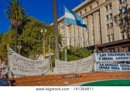 BUENOS AIRES, ARGENTINA - MAY 02, 2016: the flag of Argentina surrounded by protest banners claiming the falkland islands.
