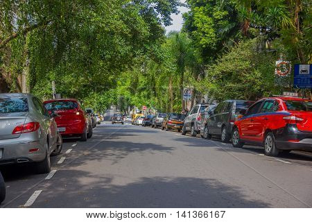 PORTO ALEGRE, BRAZIL - MAY 06, 2016: cars parked on the side of the street, nice big trees in the sidewalk