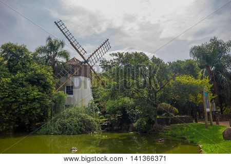PORTO ALEGRE, BRAZIL - MAY 06, 2016: nice and old windmilllocated close to a little lake with animals.