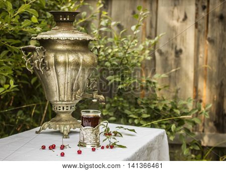 vintage copper samovar in a cup holder and a glass of hot tea stands on the table covered with a white tablecloth are scattered beside cherry and raspberry in the Russian village outdoors