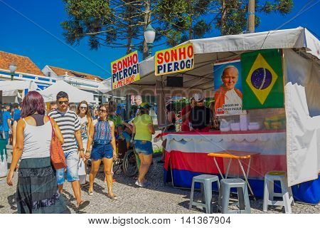 CURITIBA , BRAZIL - MAY 12, 2016: unidentified people walking next to a market stand with a photo of the pope next to a brazilian flag.