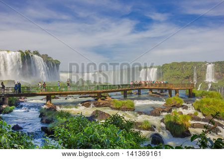 IGUAZU, BRAZIL - MAY 14, 2016: little bridge over the river close to the bottom of the falls, lot of people taking pictures of the waterfalls.