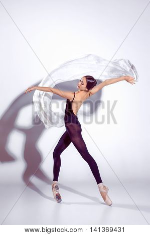 Ballerina in black outfit posing on toes, studio gray background.