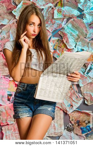 a beautiful girl with long brown hair is reading a newspaper, standing in the unusual background of newspapers