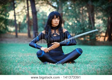 Beautiful girl sitting on the grass and holding samurai sword. Original cosplay character