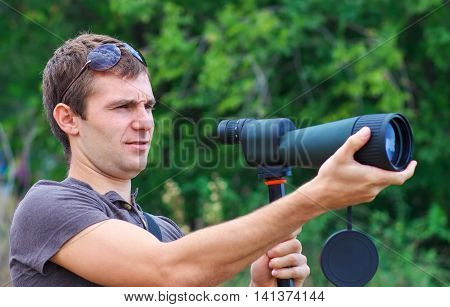 Man with spotting scope looks at the target. Positive man with telescope