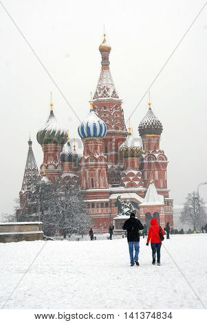MOSCOW - MARCH 15, 2013: Extreme snowstorm in Moscow. View of the Red Square and Saint Basils cathedral. People walk on the snow.