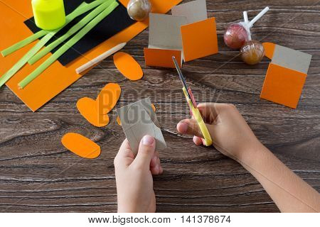 The Child Create A Greeting Packaging For Lollipop On Halloween Pumpkin Paper, Bend The In The Paper
