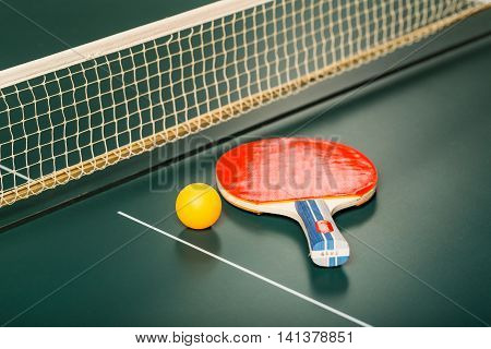 Table Tennis Racket and Ball on Table with Net