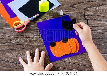 The Child Create A Greeting Card Halloween Paper Black Cat In Pumpkin, Pasting Paper Parts. Glue, Sc