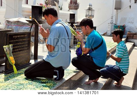 Saraburi Thailand - January 8 2013: Three Thai men their hands clasped in prayer and holding incense sticks praying at Wiat Phra Phutthabat *