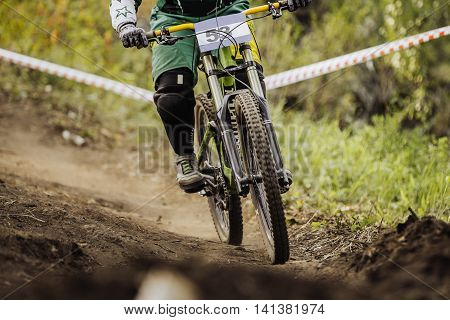 racer on bike rides forest trail during race downhill