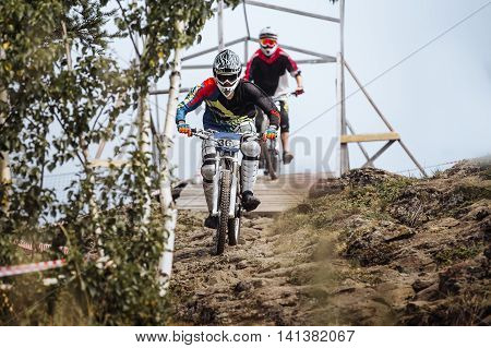 two athletes on bikes riding on a mountain trail during race downhill